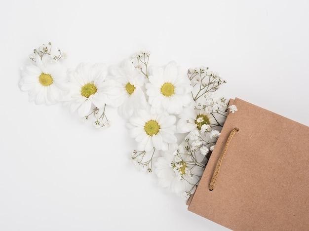 Margaridas em uma vista superior de saco de presente de papel