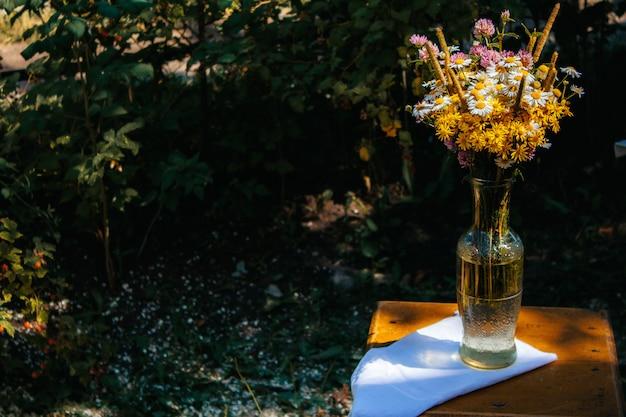 Margaridas, trevo, flores amarelas, grama sedge em um buquê de campo estão em um vaso no jardim em uma cadeira