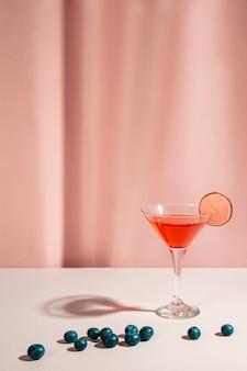 Margarita clássico cocktail com limão e bagas azuis riped na mesa branca