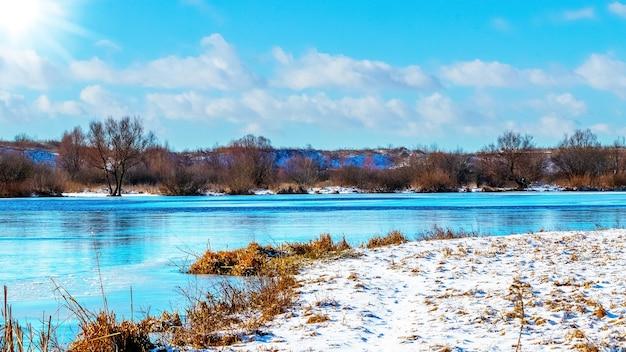 Margem de rio coberta de neve e rio com água azul em tempo ensolarado