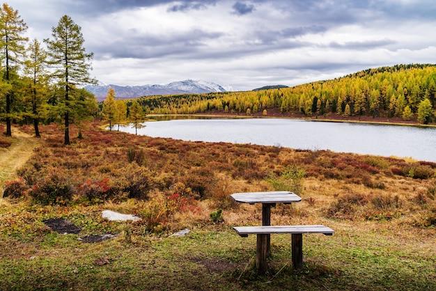 Margem do lago kidelu e picos nevados do cume kurai paisagem montanhosa de outono altai rússia