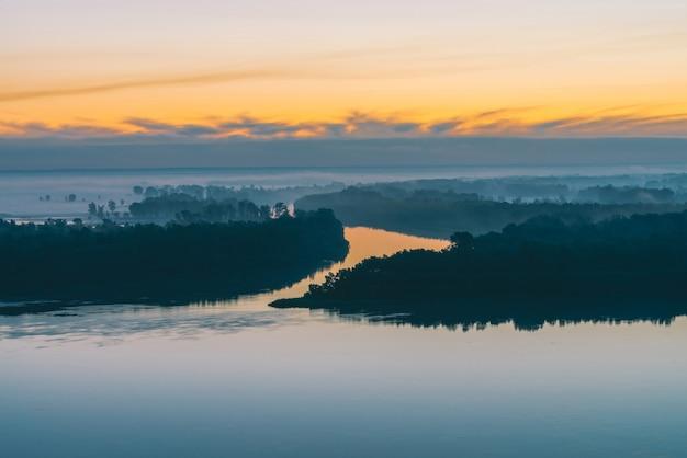 Margem do rio com a floresta sob o céu antes do amanhecer