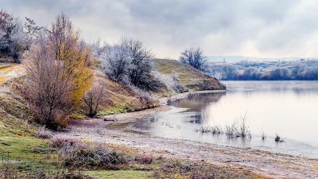 Margem do rio com árvores cobertas de geada, paisagem de outono