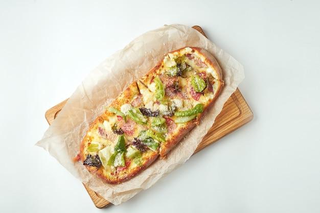 Margherita de pizza recém-assados com alface, parmesão, biscoitos e frango em uma bandeja de madeira sobre uma mesa cinza. cozinha italiana
