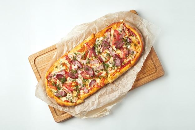 Margherita de pizza recém-assados com salsichas defumadas, bacon, molho vermelho e mussarela em uma bandeja de madeira sobre uma mesa cinza. cozinha italiana