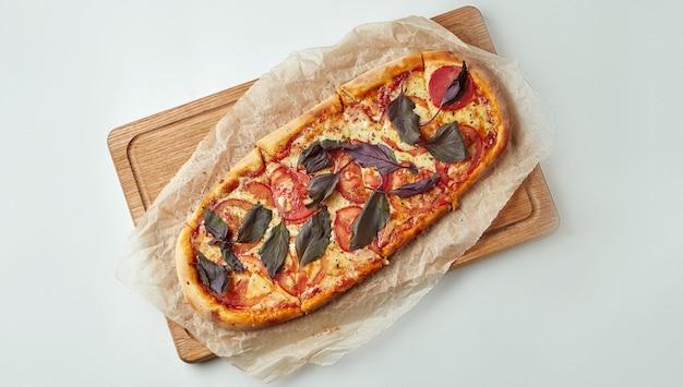 Margherita de pizza recém-assados com tomate, queijo e manjericão em uma bandeja de madeira sobre uma mesa cinza. cozinha italiana