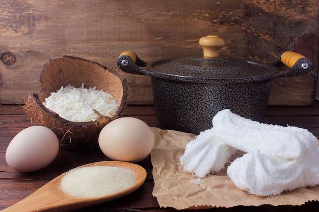 Maria-mole é um doce típico brasileiro feito com açúcar, clara de ovo, gelatina incolor e coco ralado, sobre mesa de madeira rústica