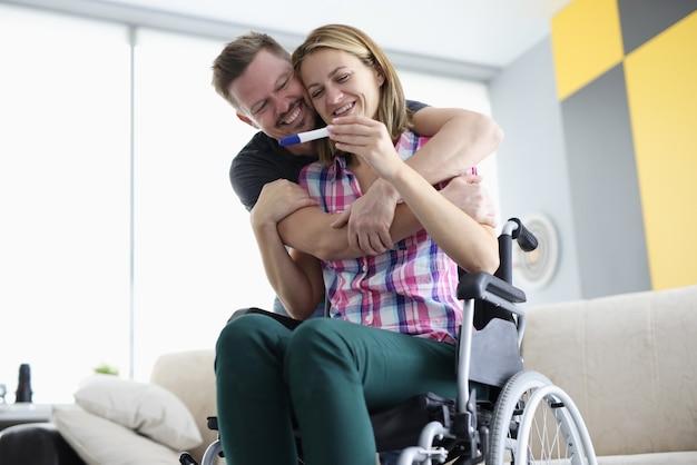 Marido abraça a esposa na cadeira de rodas pelos ombros com teste de gravidez positivo