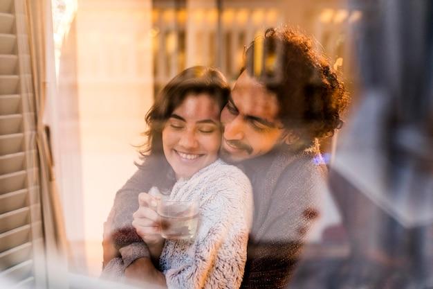 Marido abraçando a esposa enquanto ela segurava uma xícara de chá em casa