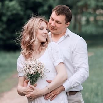 Marido abraçando a esposa grávida para um passeio no parque. o conceito de felicidade familiar