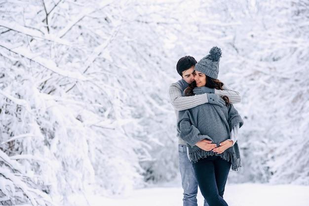 Marido abraçando ternamente sua linda esposa grávida em um parque de inverno nevado
