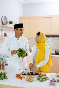 Marido ajuda a esposa na cozinha. casal muçulmano asiático preparando o jantar juntos. jovem romântico e mulher se divertem fazendo comida em casa