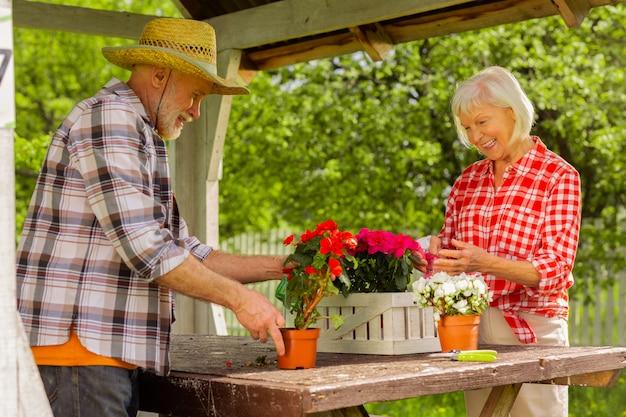 Marido ajudando a esposa. aposentado barbudo com chapéu de palha ajudando a esposa a regar flores em vasos