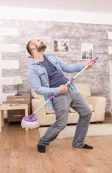 Marido alegre dançando e limpando o chão do apartamento