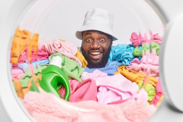 Marido alegre de pele escura usando panamá em poses de cabeça de dentro da máquina de lavar parece positivo a roupa tem um dia agitado sobrecarregado com roupas sujas multicoloridas