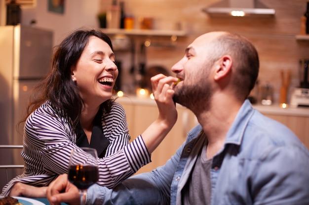 Marido alimentando a esposa com uvas durante um jantar romântico celebrando o relacionamento. esposa e marido comemorando aniversário com vinho tinto, momentos de ternura à luz de velas na cozinha.