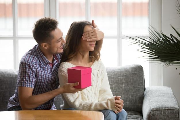 Marido amoroso fechando os olhos da esposa apresentando presente surpresa romântico