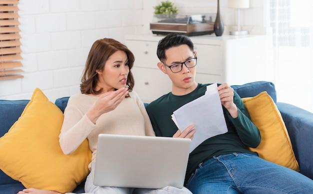 Marido asiático sério verificando as contas de serviços públicos do extrato de análise, sentados juntos em casa.