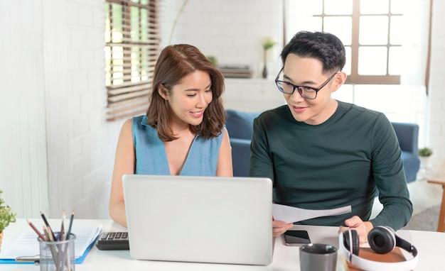 Marido asiático sério, verificando as contas de serviços públicos do extrato, sentados juntos em casa.