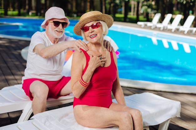 Marido atencioso colocando protetor solar em sua esposa enquanto toma banho de sol perto da piscina