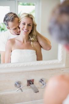 Marido beijando a esposa no pescoço no banheiro