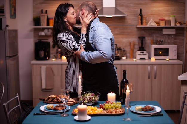 Marido beijando esposa encantada enquanto celebra seu relacionamento na cozinha com comida saborosa. homem preparando um jantar festivo com comida saudável, cozinhando um jantar romântico para sua mulher,