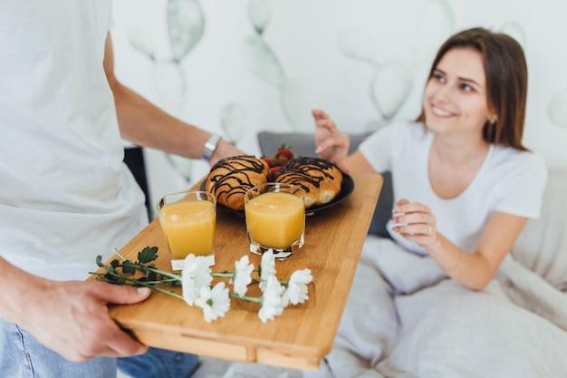 Marido bonito trouxe croissants e suco para sua esposa pousada na cama.