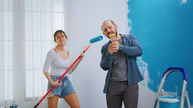 Marido cantando no pincel enquanto redecora o apartamento com a esposa alegre. redecoração de apartamento e construção de casa durante a reforma e melhoria. reparação e decoração.