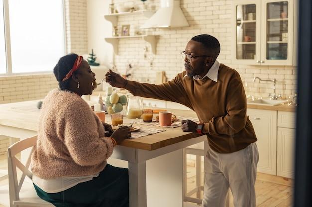 Marido carinhoso. homem afro-americano simpático a dar comida à sua mulher, ao mesmo tempo que mostra o seu carinho e apoio