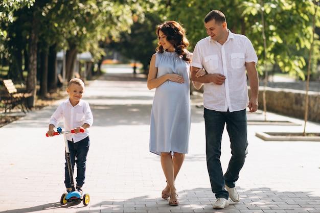 Marido com a esposa grávida e seu filho no parque