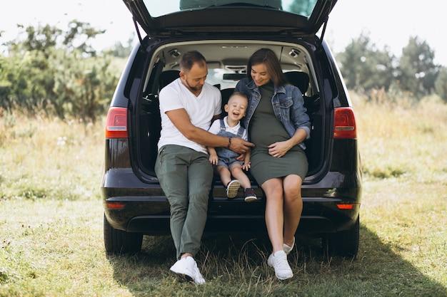 Marido com a esposa grávida e seu filho sentado no carro