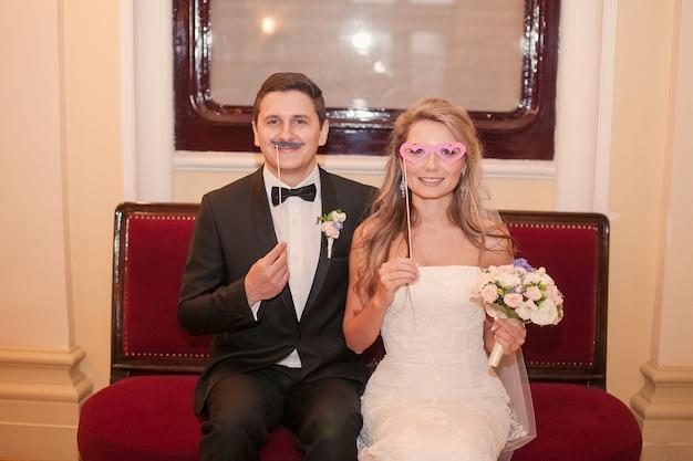 Marido com um bigode falso e mulher com um falso óculos