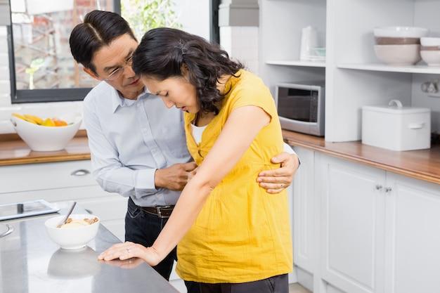 Marido, cuidando de sua esposa grávida de sofrimento na cozinha