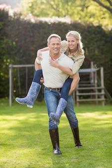 Marido dando porquinho de volta para a esposa no jardim