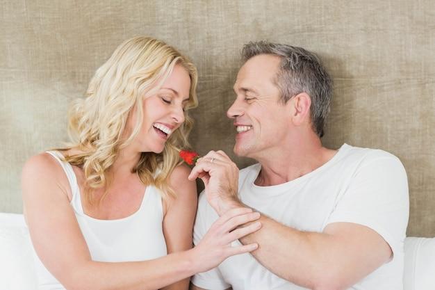 Marido dando um morango para esposa no quarto dela