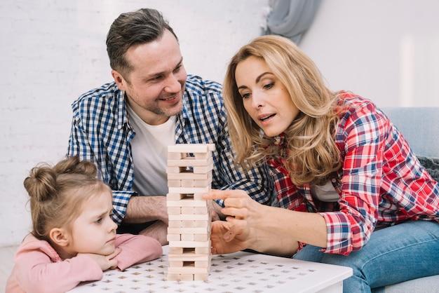 Marido de sorriso que olha sua esposa ao arranjar a torre de jogo de madeira do bloco