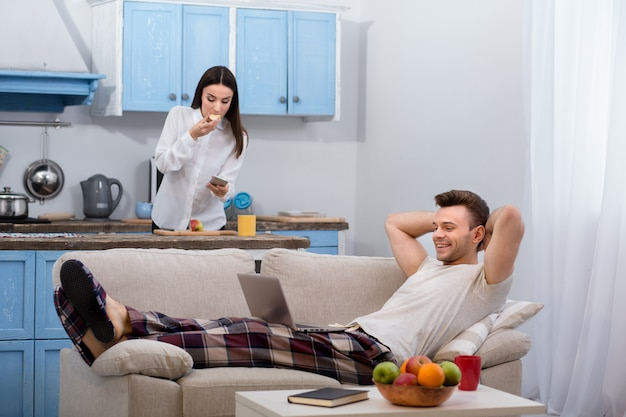 Marido deitado no sofá enquanto sua esposa está se preparando para ir trabalhar.