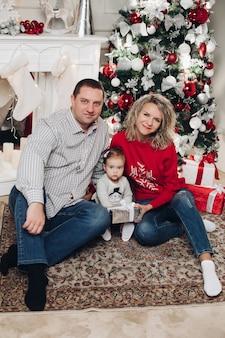 Marido e esposa beijando no sofá com a filha pequena em presentes pela árvore de natal.