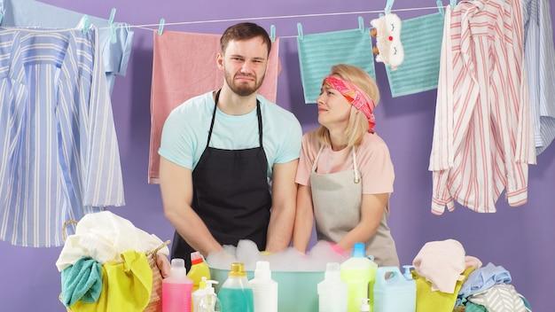 Marido e esposa estão cansados das tarefas domésticas. roupas lavadas penduram em prendedores de roupa