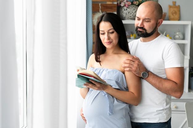 Marido e esposa grávida à procura de nomes de bebês