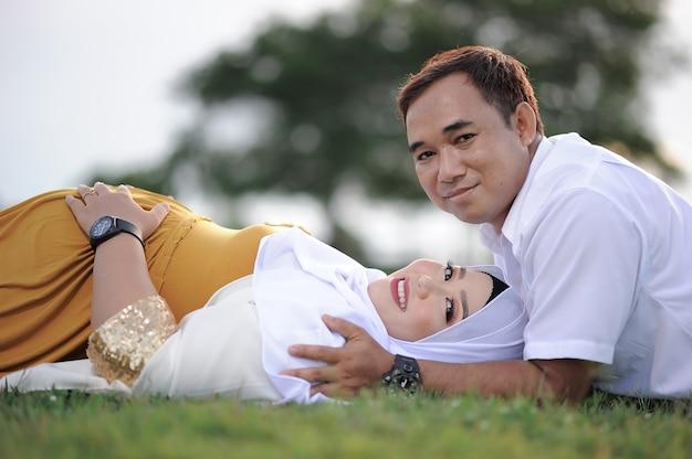 Marido e esposa grávida deitada na grama