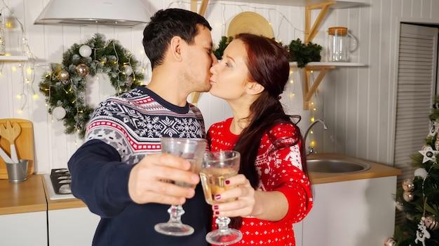 Marido e esposa morena comemoram com taças de champanhe, parabenizando e se beijando, closeup
