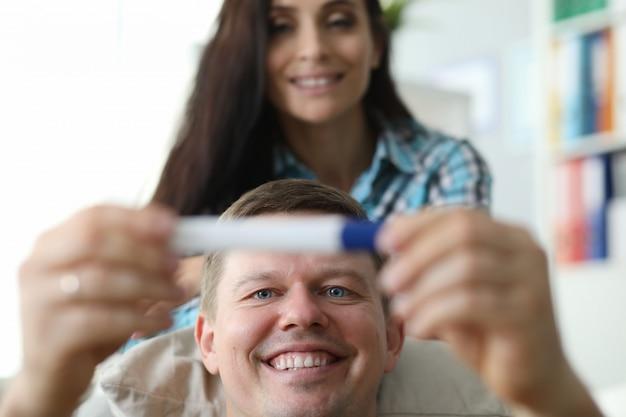 Marido e esposa se regozijam no testemunho de gravidez.