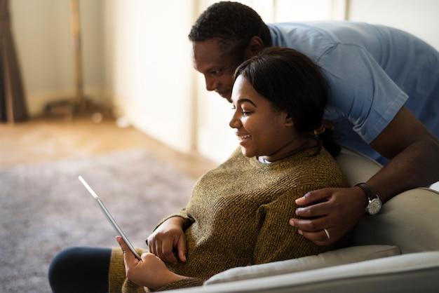 Marido e mulher afrodescendentes descansando em casa, usando um tablet juntos