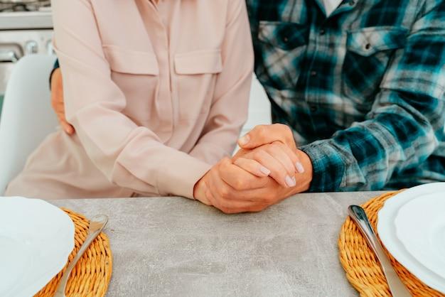 Marido e mulher aposentados se abraçam em casa