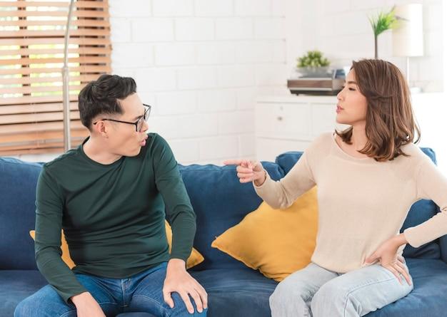 Marido e mulher asiáticos discutindo e com raiva no sofá na sala de estar em casa. problema doméstico na família.