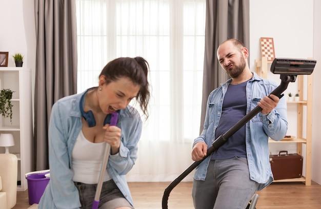 Marido e mulher cantando juntos enquanto limpam o apartamento