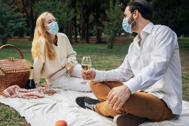 Marido e mulher com máscaras médicas fazendo um piquenique juntos