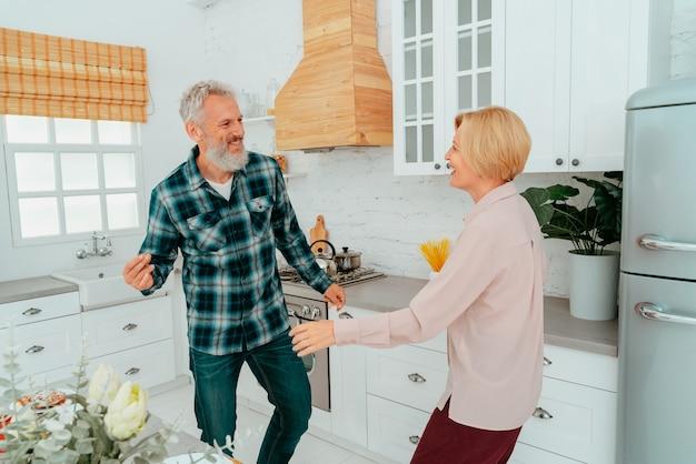 Marido e mulher dançam em casa durante o café da manhã