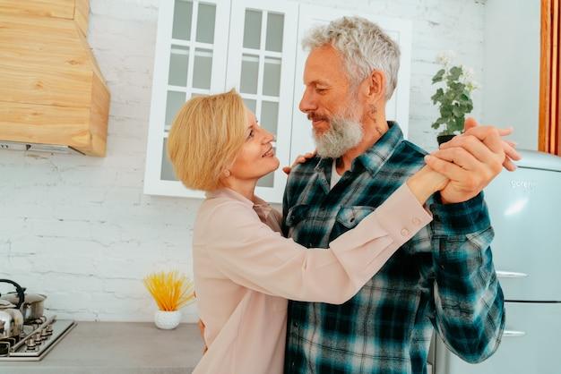 Marido e mulher dançam em casa durante o café da manhã Foto Premium